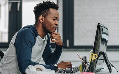 Zwarte man zit achter computer